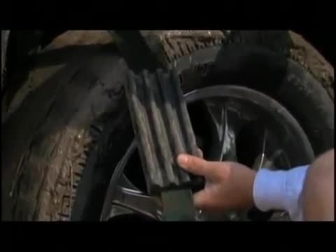 در آوردن اتومبیل گیر کرده در شن به کمک لاستیک رفع گیر