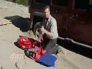 در آوردن اتومبیل گیر کرده در شن با کمک جک بادی