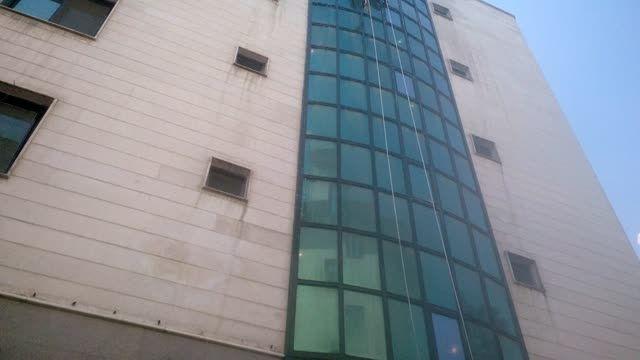 شستشوی شیشه نمای ساختمان توسط تیم کار در ارتفاع آسمان
