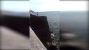 شیرجه هولناک و فرود با شکم از بالای صخره درون آب